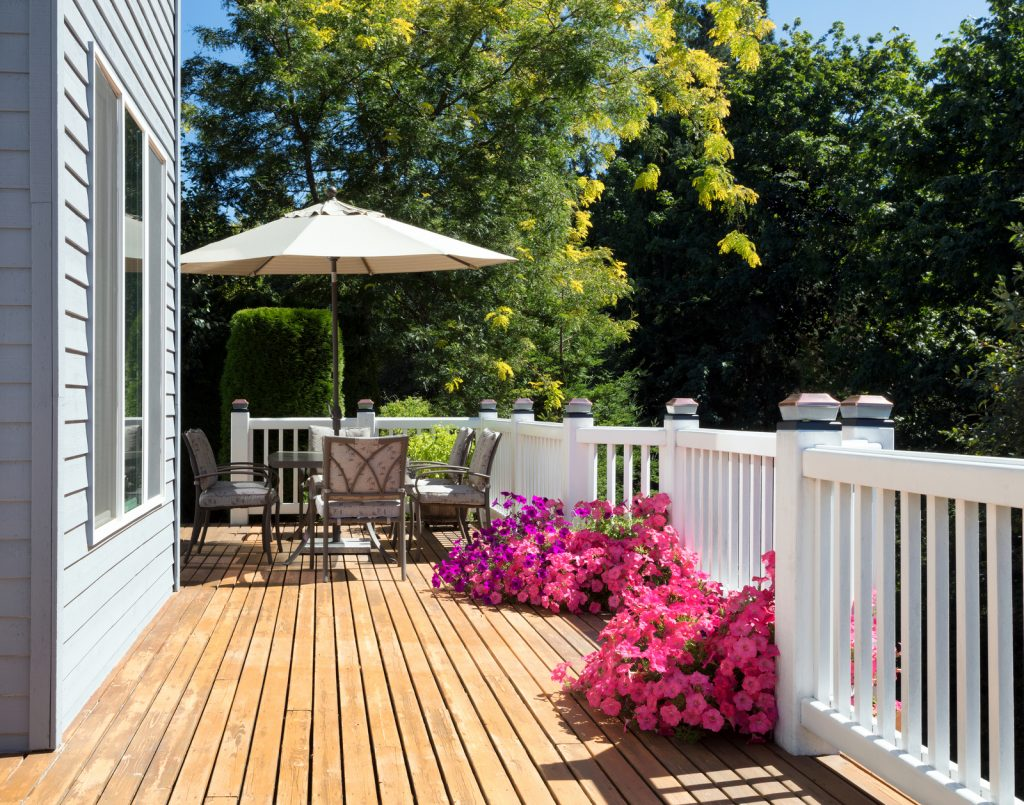 wood deck with chairs, table and flowers