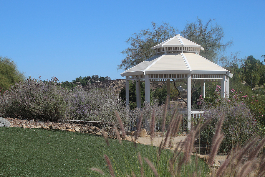 aesthetic white gazebo surrounded with plants and flowers